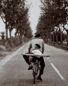 Black and white photo: man and child on bike with baguette