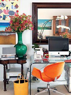 Os móveis novos e os antigos convivem em meio às obras de arte e muita cor, neste cantinho do escritório de apto em São Paulo.
