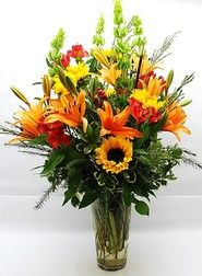 """Make them say """"WOW!"""" with this Impressive Fall Arrangement Designed to make a Huge Statement for any Occasion. Overflowing with the Colors of Autumn including Orange Lilies, Yellow Sunflowers, Red Alstromeria & Hypericum..."""