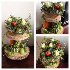 Etagère met herfstbloemen en kalebassen.
