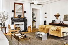 The living room's 1960s American club chairs are upholstered in an Edelman suede, the mirror and woven chair are midcentury French, the marble mantel and pair of lamps are 19th century, and the kilim is from ABC Carpet & Home.