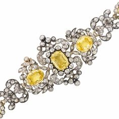Antique Silver, Gold, Yellow Sapphire and Diamond Bracelet.  5 cushion-shaped & oval yellow sapphires ap. 16.50 cts., old-mine diamonds ap. 9.00 cts., 3 diamonds missing, ap. 22 dwts. Length 6 1/2 inches. With fitted box.