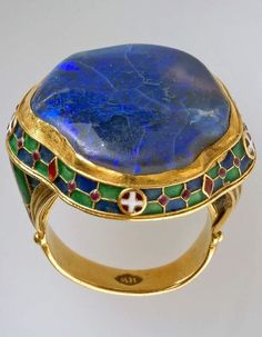 An Arts and Crafts gold, enamel and opal ring, by Henry Wilson, London, early 20th century. Set with a large black opal, enamelled round edge of bezel and on shoulders. #HenryWilson #ArtsAndCrafts #ring