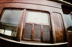 Detalhe da janela do vagão de 1928, em madeira, com venezianas e vidros jateados com a logomarca da ferrovia (SPR, São Paulo Railway).