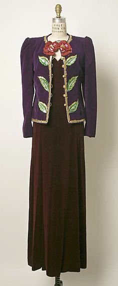 "Evening suit by Yves Saint Laurent, French, fall/winter 1978-79. Burgundy silk velvet strapless dress with gold-thread embroidery at neckline, and embroidered purple silk velvet jacket with sequins and rhinestones. Label: ""YVES SAINT LAURENT / PARIS / MADE IN FRANCE / 45298"""