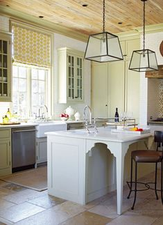 Stylish Islands for Traditional Kitchens - gleaming white island, limestone flooring has patina of old tile, love the wood ceiling