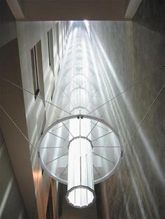 Morgan Lewis Offices, Washington DC, Architect: Carpenter & Norris Consulting, New York. A multiple mirror system directs the sunlight into a specially designed light tube. This allows the light to spread downwards and horizontally into the deep internal space_roof-mounted heliostat directs light down a 14-story atrium.