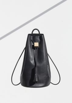 Building block backpack  - Smooth unlined black leather, Leather lined base, Rubber shoulder strap, Leather tassel, Wood block cinch closure H 38 cm × W 34 cm × D 20 cm