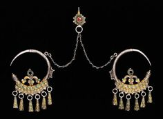 Africa | Ear pendants made by Moroccan Jewish craftsmen. | Early 20th century | Silver alloy, enamel, glass, carnelian | Silver jewelry is considered portable wealth throughout the mountainous Atlas region of Morocco. Women wear impressive displays of elaborate jewelry during important public gatherings, especially weddings, where silver symbolizes honesty and purity.