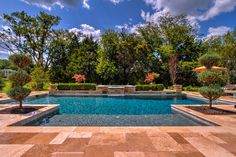 Formal pool design, midnight blue surface, pavers, raised wall with flower pots. Beautiful!