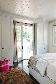 custom floor-to-ceiling cabinets flanking a French door provides valuable storage in this bedroom