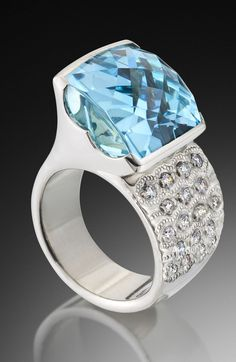 A modern ring design by Adam Neeley.  La Mer Aquamarine Ring is compelling and fresh. In this unique ring design, a stunning and distinctively-cut aquamarine is asymmetrically set in white gold with diamond accents. This aquamarine was cut by the incredible lapidary artist, Stephen Avery.