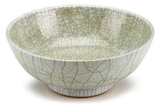 """Chinese ge-type celadon earthenware bowl     18th century     The wide footed bowl of typical form and with """"iron wire and golden thread"""" craquelure throughout the pale celadon glaze.     H: 4 in. D: 9 3/4 in."""