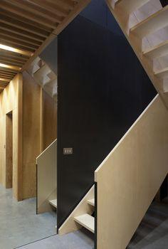 Frame House   Jonathan Tuckey Design, Holland Park, London, UK. Birch ply staircase, stairwell lined in black valchromat.