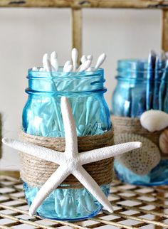 Give your bathroom decor a makeover with this beautiful DIY Beach Themed Bathroom Mason Jar Storage Set that features shells and beach colors.