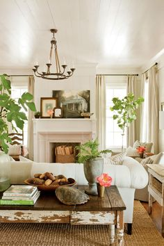 A fresh living room paired w/ a rustic console table behind the couch really adds something extra to this space. And get a load of all those plants!