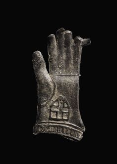 Pilgrim-badge; lead alloy; brooch, pin missing; form of single glove of Becket; shield with plain cross.