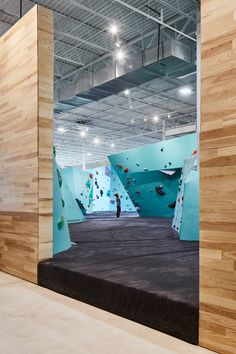 The bouldering zone unfolds in an open space beneath the high industrial-style roof. A series of faceted structures, which vary in size and shape but are all coloured turquoise, are peppered with multi-hued holds that offer climbing for all abilities.