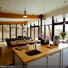 In der Wohnküche sorgt die Holzarbeitsplatte für ein natürliches Ambiente. Auch der restliche Raum mit Ess- und Wohnbereich setzt den Schwerpunkt auf das  …