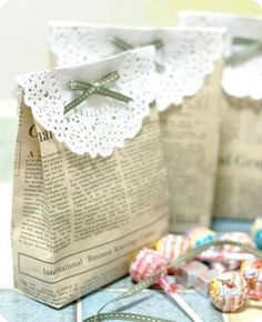 Newspaper gift bags topped with paper doilies and a bow ~ beautiful,  unique and economical gift wrapping!