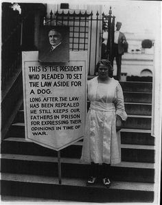"19 July 1922. Young women picketing outside White House gates for amnesty for war protesters - sign, with portrait of Harding, reads: ""This is the president who pleaded to set the law aside for a dog. Long after the law has been repealed he still keeps our fathers in prison for expressing their opinions in time of war"""