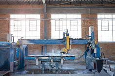 Female worker operating big stone cutting machine