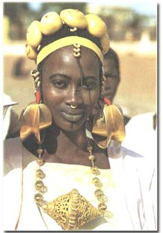 The Fulani women of West Africa wear large gold earrings called kootone kange. They flaunt dark tattoos around their lips and embellish their braided hair with gold coins.
