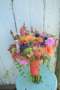 Coral, pink and blue colors combine beautifully in this August wedding bridal bouquet. Design by Buckeye Blooms www.buckeyeblooms.com