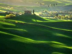 The Sun rises over green fields in Tuscany, Italy.
