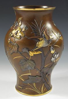 "A splendid example of the master metalworker's art, this remarkable full- bodied vase with gold rims utilizes the precious metals gold and silver, together with the subtle alloys shakudo and shibuichi. Suzuki Chokichi signature and double-mountain mark on base. Height, 10.25"". Meiji Period. Japan."