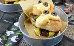 "<p>A zesty cannellinni bean patty is slathered with vegan mayo and topped with buns and a deliciously cheese sauce ""face,"" mini pickles for ""fangs,"" and black olives for ""eyes.""</p>"