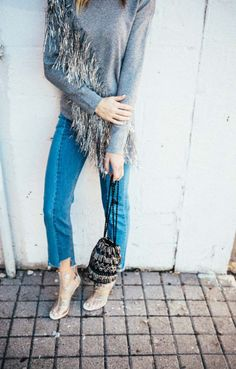 Grey fringe sweater, black beaded bucket bag, and clear heels