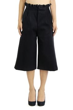 Black, stretch cotton twill culottes featuring front side pockets, front zipper, and a ruffled waistband. Culottes meant to fall mid-shin.