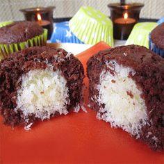 A lisztbe beletesszük a kakaóport, a cukrot, a sütőport és összekeverjük, majd hozzáadjuk az étolajat, az egész tojásokat és a joghurtot. Az egészet jól összekeverjük, hogy egy kicsit folyós tészta masszát kapjunk.  A kókuszreszelékbe belekeverjük a porcukrot és a margarint. A muffin sütőformába belehelyezzük a muffin papírokat, és az aljába 1 evőkanál tészta masszát csurgatunk. A kókusz keverékből a kezünkkel kis golyót formálunk és a csurgatott tészta massza közepébe helyezzük, majd 1…