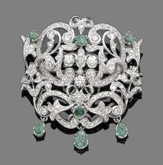 An emerald and diamond pendant/brooch, 1971 The openwork cartouche set throughout with brilliant and single-cut diamonds, highlighted with circular-cut emeralds, suspending three pear-shaped emeralds, to a venetian-link chain