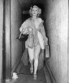 Sonia Stacpoole, a scantily-clad member of the Windmill cast makes her way along a narrow corridor to the theatre air raid shelter clutching a tin-hat and a pillow. everyday, 1941.
