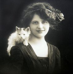 Edwardian woman c.1910s with a sweet little kitten. Such a lovely portrait! I love how people wanted to be photographed w\/ their pets. But in this case I think it was the photog's kitten. So successful too; how can you be tense with a kitten on your shoulder? You can't! This was prob at the beginning of the shoot then he\/she did shots w\/out the studio kitten. [I'm certain the img was square; it would have been large format (bellows camera) with 4x5\ or 8x10\ negatives.)