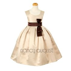 Sweet Alice Champagne Flower Girl Dress: This champagne flower girl dress is sweet and simple. It's a great choice for all the little girls who don't fancy the frilly puffy dresses. Additionally, this dress is made with elegant dull satin featuring a sleeveless bodice, triple pleated shoulder straps, a u-scoop neckline, a streamlined pleated A-line skirt, and a contrast waistband that has an off-centered vertical bow adorned to the side.