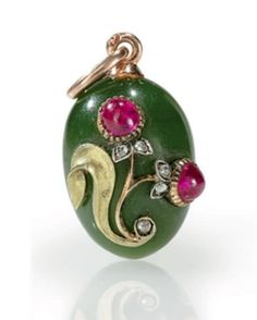 A Jeweled Gold-Mounted Nephrite Egg Pendant  By Fabergé, with indistinct workmaster's initials, probably for Michael Perchin, St. Petersburg, 1896-1903 Ovoid, the hardstone body applied with a gold leaf and a flower set with two cabochon rubies and rose-cut diamonds, with gold suspension loop, marked on suspension loop 1/2 in. (1.3 cm.) high