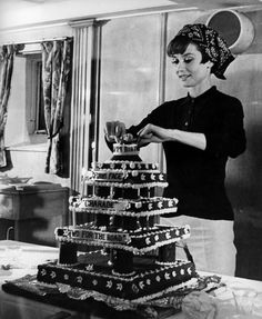 Audrey Hepburn applies the final touches to a birthday cake for director and friend Stanley Donen, April, 1967.