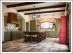 exposed rafters, cast iron fixtures,  tile work, arched window and open light, tile allows reflection to light space, warm feel of ceramic floors, recessed lighting, arches, bold red accents, glass door covers
