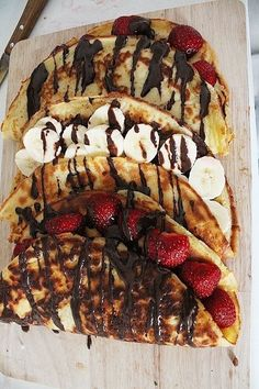 Banana and strawberry crepes drizzled with chocolate