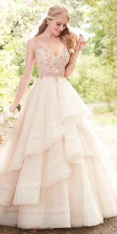 Photo: Flirty and feminine, this Martina Liana Spring 2017 pink wedding dress with rose gold beading is a dream come true for the modern princess bride! The bodice of this Tulle gown features soft, scroll beadwork that extends through the straps on to the scoop back, giving the illusion the straps are floating. Pearl beads are scattered throughout, adding to the feminine style. A full, tiered ball gown skirt gives this wedding dress a glamorous feeling, while a full train completes the…