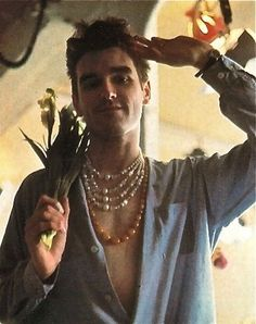 In the early 1980s the Smiths popularized jewelry for men, reviving a hippy trend from the 1960s.  In a then-sexist Britain, it was a bit of a shock to see men wearing ropes of beaded and jewelled necklaces, and even wielding bunches of beautiful flowers in nightclubs and pubs. In the photo Morissey, the band's star, looks great in his layered necklaces! Well done, Morrissey!