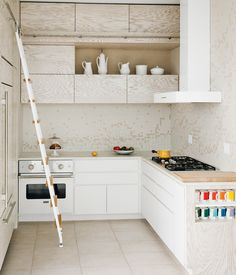 """To complement the white-washed custom cabinetry in her kitchen, architect Julie Salles Schaffer designed a tile backsplash to resemble """"m..."""