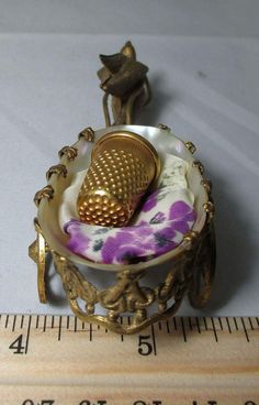 This is a Palais Royal, Brass Thimble Holder carriage lead by a DOVE. The shell is Mother-of-Pearl outlined in brass with a lovely floral cushion in