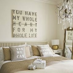 This bedroom looks SOOO relaxing. I love everything about it...the rustic wall art, elegan chandelier, pillows with messages, color scheme!  <3