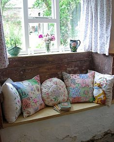 You've got to have a window seat. I like the damaged/distressed looking wood and walls with the sweet comfy floral pillows.