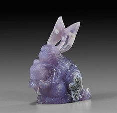 <b>CHALCEDONY RABBIT PAIR CARVING</b> <br  /> <i>Artist: Ronald Stevens <br  /> West Java</i> <br  /> Mother keeps close to her little one as it nibbles on some food, in this charming little carving. Each has large ears and lovely lavender coloring, enlivened in places by patches of natural pale blue agate patterning. It measures 2 3/4 inches high with a lacquered wood stand.