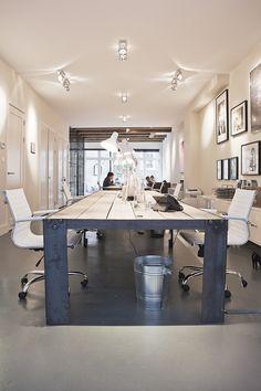 Het interieur in deze kamer is er staat een grote tafel met stoelen. Er hangen een paar lampen, Er staat een prullenbak. Veel is wit. Er staan achterin de kamer wat planten. Er hangen een heleboel schilderijtjes en schilderijen aan de muur.